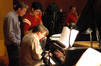 Pianist Gary Nesteruk and orchestrator Sean McMahon observe as Christopher Young reworks a cue at the piano