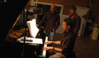 Brian Tyler makes some adjustments to the score on the piano as music editor Joe Lisanti and director Jonathan Liebesman observe