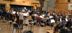 The orchestra performs under composer and conductor Fil Eisler