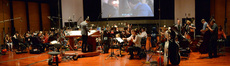 The orchestra waits as the next clip is prepared
