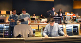 J.J. Abrams and Michael Giacchino look at a cue while the rest of the booth works