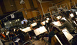 Composer Michael Giacchino and conductor/orchestrator Tim Simonec discuss a cue as the orchestra prepares to record