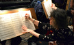 One of the violists makes a correction to her part