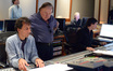 Orchestrator Jeff Atmajian looks at the score with music supervisor David Franco as scoring mixer Sylvain Lefebvre works at the console
