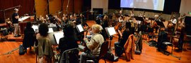 Conductor and orchestrator Tom Calderaro records a cue from <i>The Heat</i> with the orchestra
