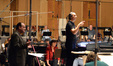 Orchestrator Conrad Pope and composer Alexandre Desplat give notes to the orchestra