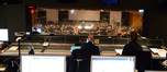Scoring mixer and producer Paul Freeman and Bob Wackerman watch composer and conductor Timothy Williams and the orchestra from the booth