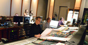 Inside the booth, orchestrator Andrew Kinney, scoring mixer Jeff Vaughn, and stage recordist Tom Hardisty listen to the playback