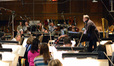 Composer and conductor Joel McNeely speaks to the orchestra