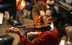 A violinist tunes her instrument