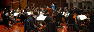 Conductor Tim Simonec and the orchestra don their headphones to record the next cue