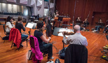 The orchestra performs a cue with composer/conductor Sherri Chung