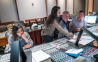 Scoring assistant Raashi Kulkarni looks over her score as composers Sherri Chung and Blake Neely go over a cue with scoring mixer Greg Hayes