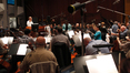 Orchestra contractor Reggie Wilson talks with the orchestra