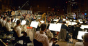 Orchestrator Tim Simonec and the orchestra record a cue