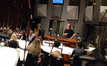 Composer and conductor John Debney and the orchestra wait for the next clip to be queued up