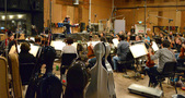 Conductor Nolan Livesay and the orchestra record a cue for <i>Almost Christmas</i>