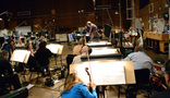 Conductor Michael Kosarin and the orchestra set up for the next cue