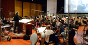 Conductor Michael Kosarin and the orchestra perform with the playback