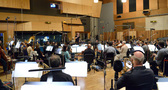 The orchestra performs with composer/conductor John Debney