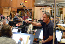 A violinist relays information to the orchestra