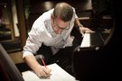 Composer Christopher Lennertz makes a note to the score