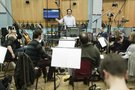 Christopher Lennertz conducts the orchestra at Abbey Road