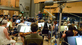Conductor Mark Graham records a cue with the orchestra