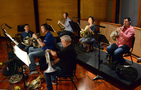 The French horn section practices between takes