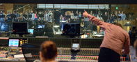 Scoring mixer Casey Stone flashes the thumbs up to choir conductor Jasper Randall that he's ready to record