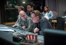 Additional music composers Aljoscha Christenhuß (partially obscured) and Antonio Di Iorio listen to a cue with composer Tom Holkenborg and scoring mixer Alan Meyerson