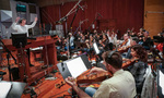 Conductor Nick Glennie-Smith records a cue with the strings