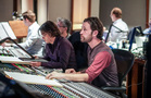 Scoring mixer Greg Hayes checks the playback as composer Heitor Pereira follows along with his score
