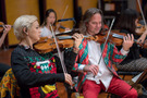 The orchestra performs in festive holiday sweaters