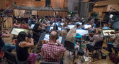 The orchestra records a cue with composer/conductor Joel McNeely