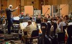 Conductor Nick Glennie-Smith and the orchestra prepare for the next take