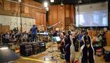 The orchestra records a cue under the baton of conductor Pete Anthony for <i>Snatched</i>