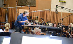 Conductor Pete Anthony goes over a cue at the podium