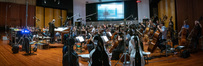 Nick Glennie-Smith conducts the orchestra on a cue from <i>Aquaman</i>