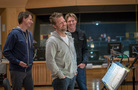 Music supervisor John Houlihan, director David Leitch and composer Tyler Bates laugh during the choir session