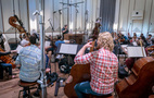 Conductor Lucas Richman records a cue with the orchestra