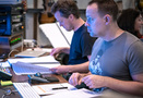 Composer Nathan Barr reviews his score as recording mixer Adam Michalak works on a cue