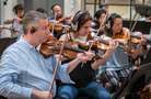 Concertmaster Mark Robertson and the violin section performs