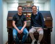 Composer Nathan Barr and Universal Film Music President Mike Knobloch sit at the organ