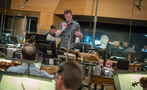 Orchestrator Nolan Livesay conducts the orchestra as composer John Paesano observes