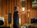 Composer Harry Gregson-Williams gives feedback to the musicians