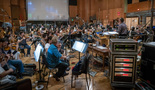 The orchestra performs a cue with conductor Gavin Greenaway