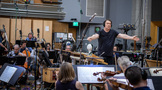 Composer David Newman cues the violin section