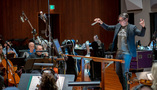 Conductor/lead orchestrator Tim Davies performs a cue with the orchestra