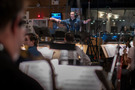 Composer Christopher Lennertz checks with the playback as he cuts off the orchestra at the end of a cue
